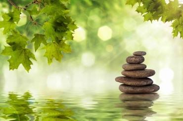 Zen rocks standing in water with ripples